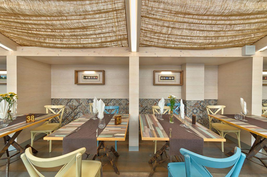 Sala esterna del ristorante con panche e tavoli all'ombra